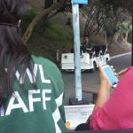 Staff driving carts and woman on her phone
