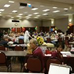 Large room full of people sat at tables with balloons