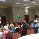 Large room with many community members sitting at tables