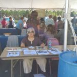 Woman sitting behind table at fair giving out information
