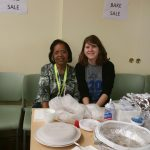 Two people behind the bake sale booth