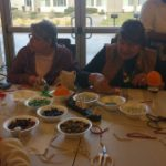 People making a bottle top wind chime craft